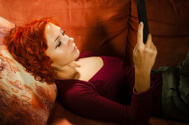 Young woman on a couch with tablet pc Free Photo