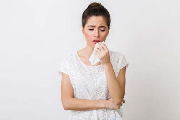 Giovane donna che tossisce con un tovagliolo, prende freddo, si sente male, isolato Foto Gratuite