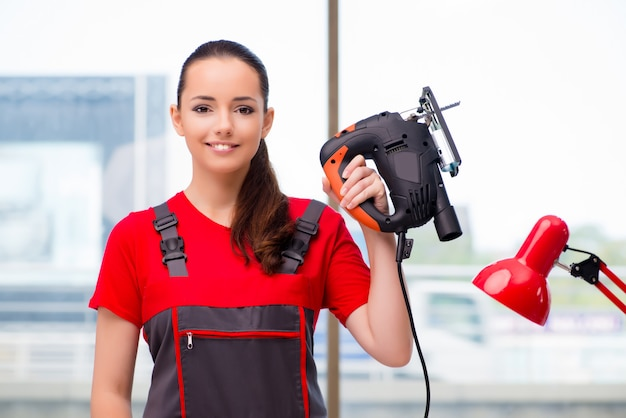 Young woman in coveralls doing repairs Premium Photo