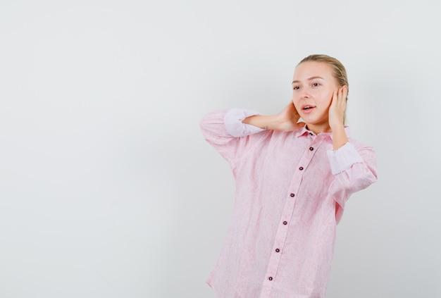 ピンクのシャツの手で耳を覆い、前向きに見える若い女性 無料写真