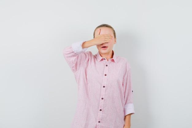 ピンクのシャツの手で目を覆う若い女性 無料写真