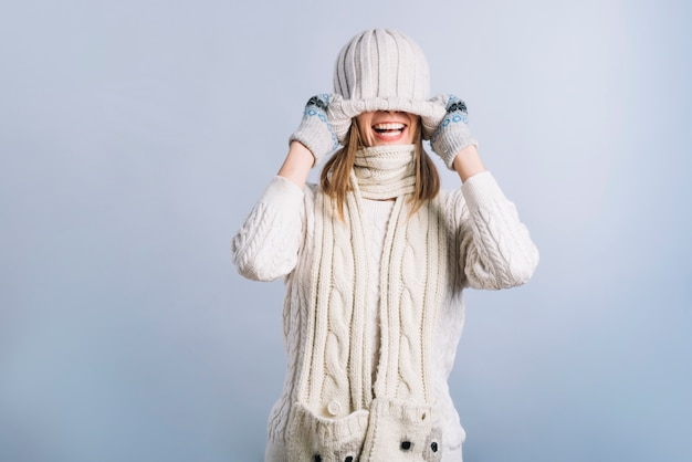 Young woman covering face with cap Free Photo
