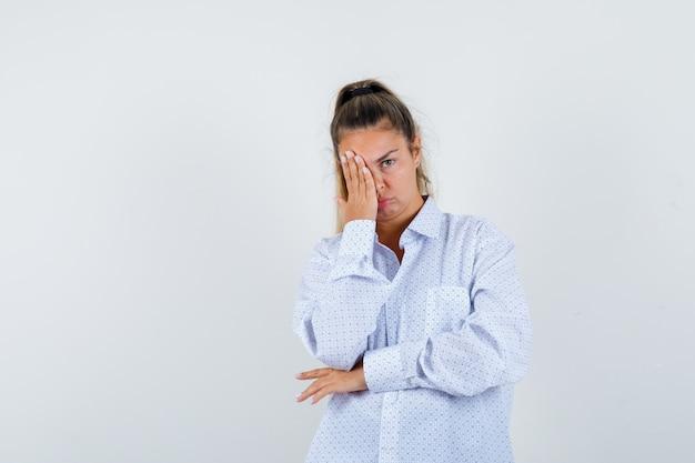 Giovane donna che copre parte del viso con la mano in camicia bianca e sembra stanca Foto Gratuite