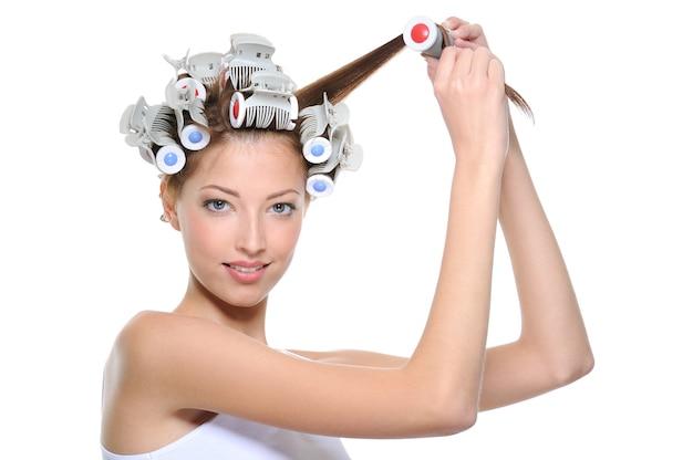 Giovane donna che arriccia i suoi capelli ai bigodini - isolati su bianco Foto Gratuite