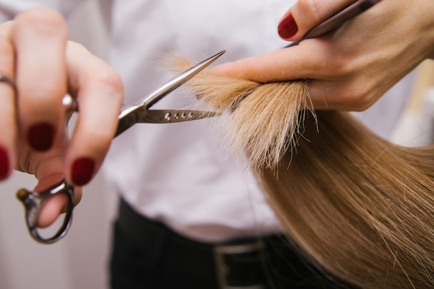 A young woman cuts her hair with scissors Premium Photo