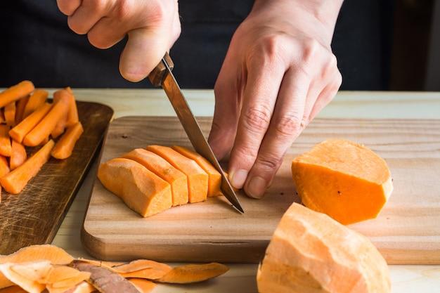 Молодая женщина резки ножом сладкий картофель в клинья кожуры на деревянный стол Premium Фотографии