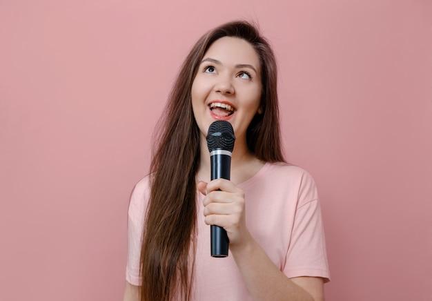 Молодая женщина балуется, прищуривает глаза с микрофоном в руке на розовом фоне Premium Фотографии