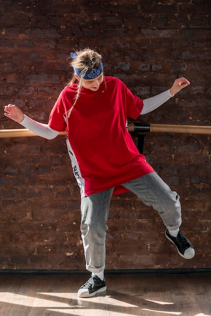 Young woman dancing in front of brick wall Free Photo