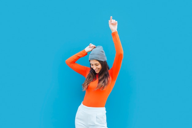 Young woman dancing with arm raised in front of blue backdrop Free Photo