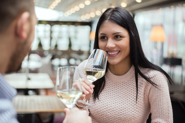 Young woman on date with man in cafe, drinking wine. Premium Photo