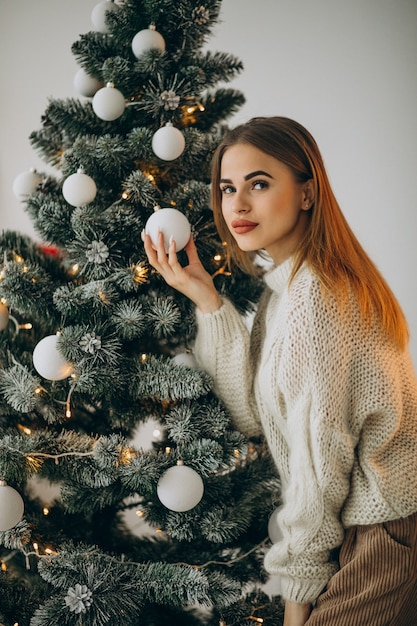 크리스마스 트리를 장식하는 젊은 여자 무료 사진