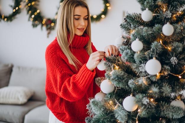 Giovane donna che decora l'albero di natale Foto Gratuite