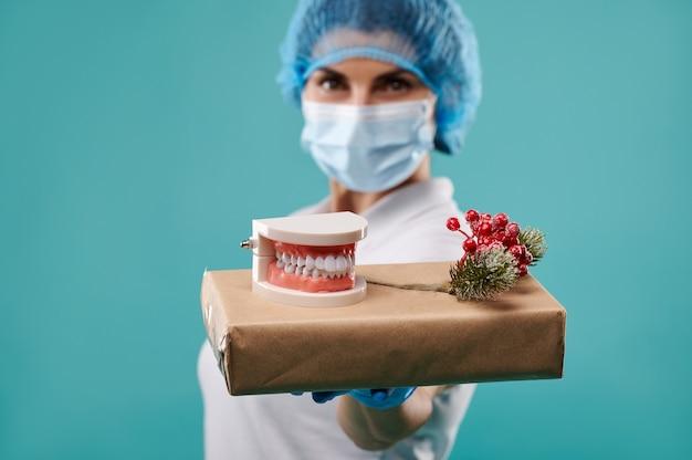Молодая женщина-дантист в шляпе и маске держит рождественский подарок на ладони. Premium Фотографии