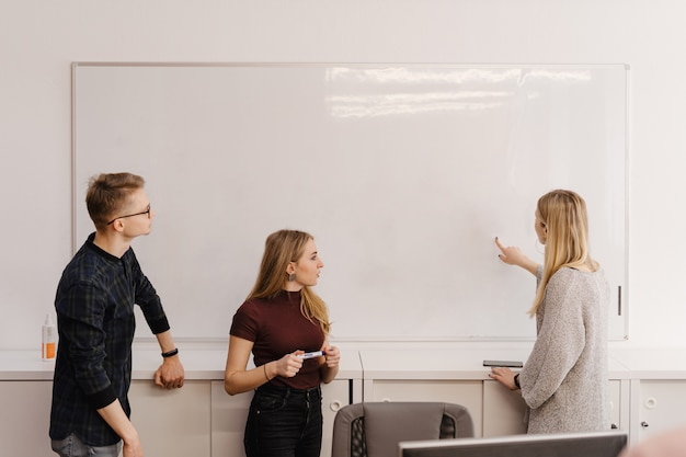 Young woman discussing with colleagues over whiteboard at office Free Photo
