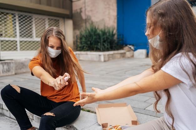ピザを食べる前に彼女の友人の手を消毒する若い女性 無料写真