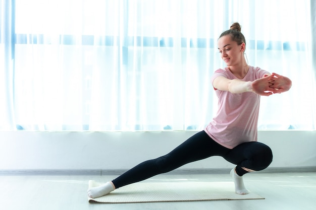 젊은 여자는 집에서 요가 매트에 근육과 피트니스 운동을 스트레칭합니다. 체중을 줄이고 건강을 유지하십시오. 건강한 스포츠 라이프 스타일 프리미엄 사진