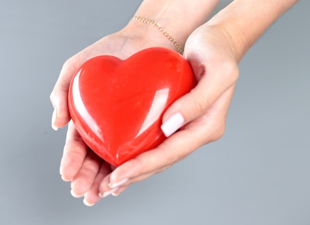 Young woman doctor holding a red heart. Premium Photo