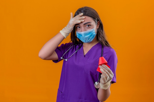 防護マスクと手袋を着用して赤いリボンを押しながら分離されたオレンジ色の背景の上に立って手で額に触れる笑みを浮かべてphonendoscopeと医療の制服を着た若い女性医師 無料写真