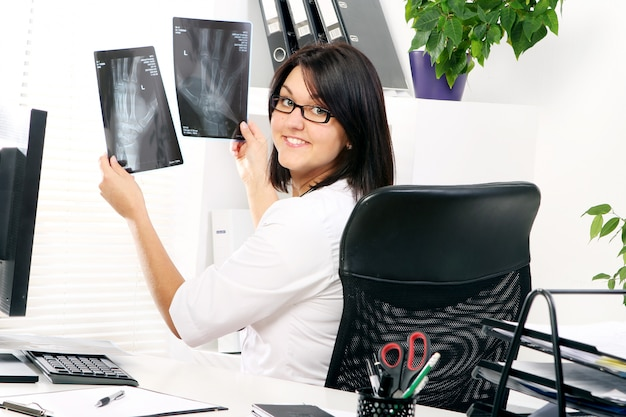 Young woman doctor is looking at xray Free Photo