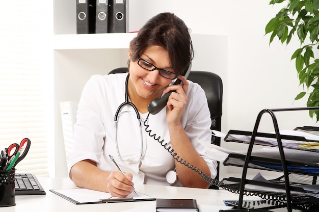 Young woman doctor talking by phone Free Photo