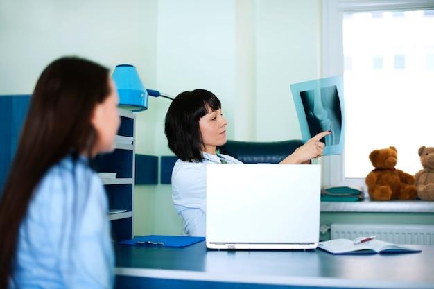 Giovane donna e medico guardando i raggi x Foto Gratuite