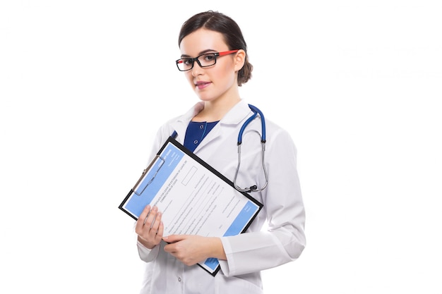 Young woman doctor with stethoscope holding clipboard in her hands in white uniform on white Premium Photo