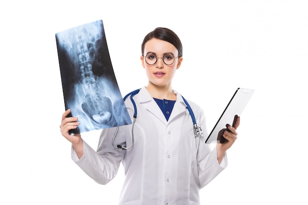Young woman doctor with stethoscope looking at x-ray making diagnosis in white uniform Premium Photo