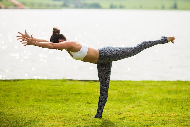 La giovane donna fa yoga posa al parco al mattino con la luce solare Foto Gratuite