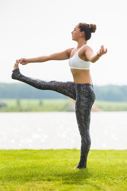 Young woman does yoga pose at the park in the morning with sunlight Free Photo