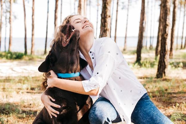 彼女の犬と一緒にピクニックをしている若い女性 Premium写真