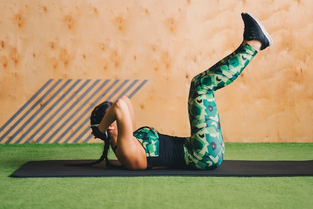 Young woman doing abs workout in a gym on a mat. Free Photo