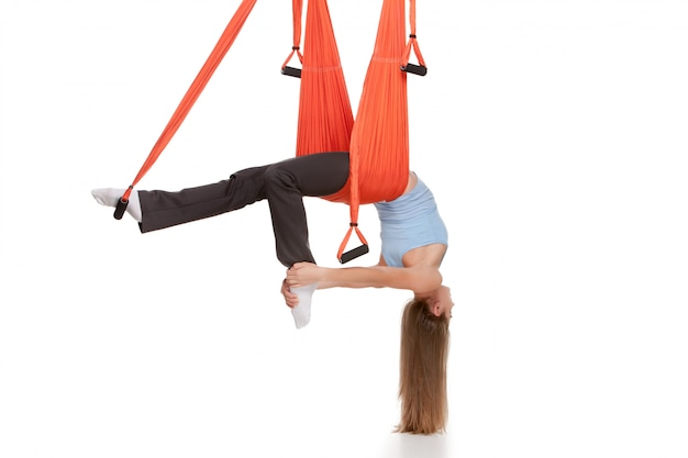 Young woman doing anti-gravity aerial yoga in hammock on white wall Free Photo