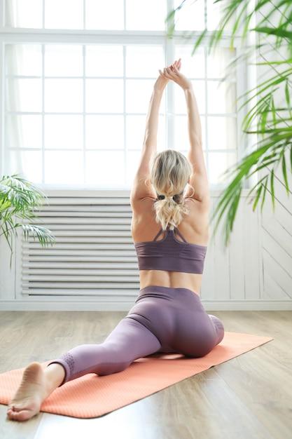 Молодая женщина делает растяжку спины и ног Бесплатные Фотографии
