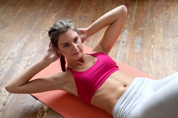 Giovane donna facendo esercizi a casa Foto Gratuite
