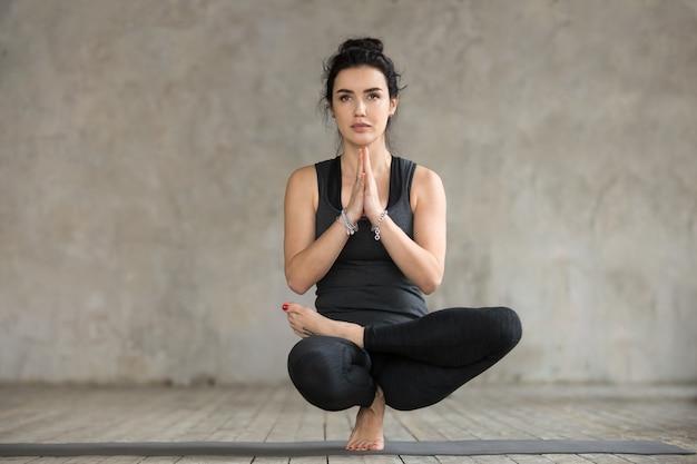 Young woman doing half lotus toe balance exercise Free Photo