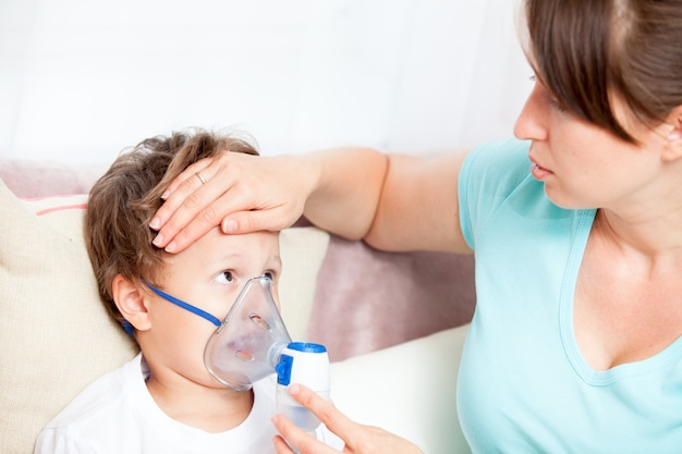 Young woman doing inhalation with a nebulizer son and touches his forehead Premium Photo