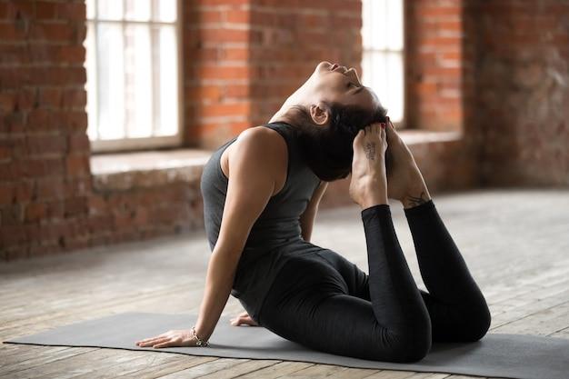 Giovane donna facendo esercizio di re cobra Foto Gratuite