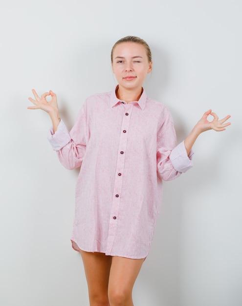 ピンクのシャツで瞑想とまばたきの目をしている若い女性 無料写真