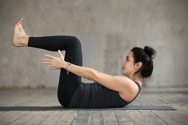 Young woman doing navasana exercise Free Photo
