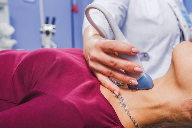 Young woman doing neck ultrasound examination Premium Photo