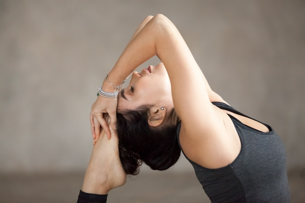 Young woman doing one legged king pigeon exercise, close up Free Photo