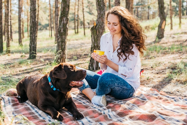 Young woman doing a picnic with her dog Free Photo