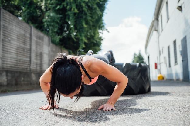 巨大なタイヤを使用して屋外トレーニングをプッシュアップを行う若い女性 Premium写真