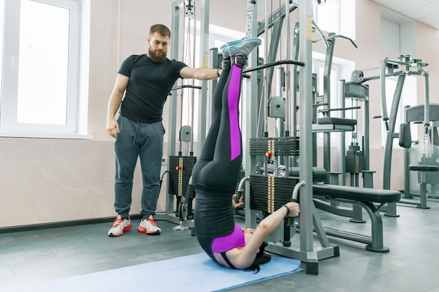 Young woman doing rehabilitation exercises with personal instructor Premium Photo