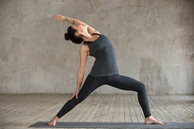 Young woman doing reverse warrior exercise Free Photo