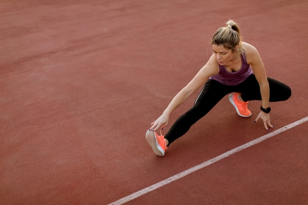 Young woman doing some exercises and streching legs at the court at outdoor Premium Photo