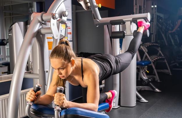 체육관, 다리 및 엉덩이 운동에서 스포츠를하는 젊은 여자 프리미엄 사진
