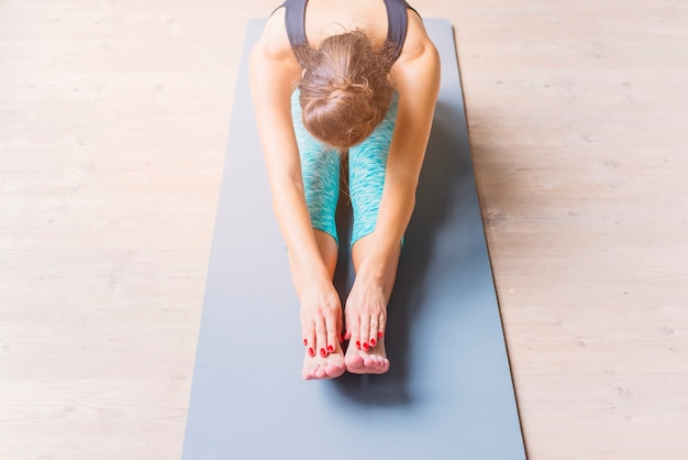 Young woman doing stretching exercise on yoga mat Free Photo