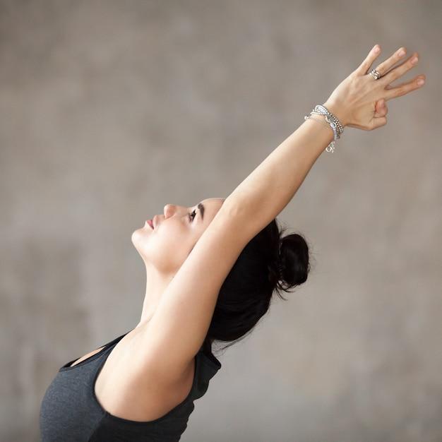 Young woman doing virabhadrasana 1 exercise Free Photo