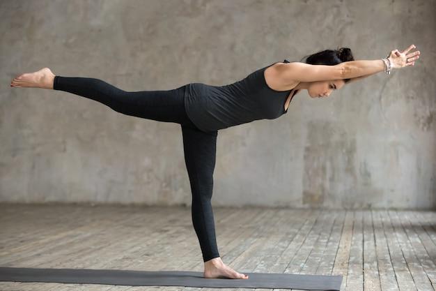 Young woman doing virabhadrasana 3 exercise Free Photo